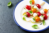 Cherry Tomato and Mozzarella Skewers with basil leaves and olive oil on a plate. Summer snack. Flat lay. Healthy food - 211143221