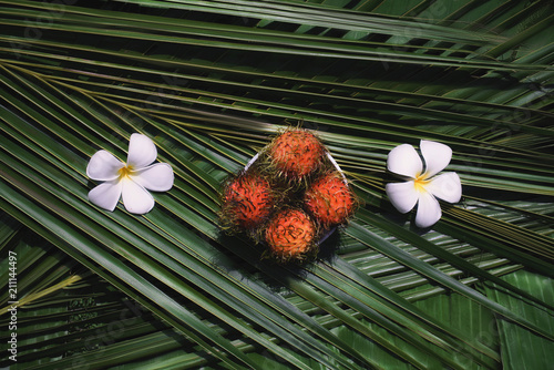 Fotobehang Plumeria Rambutan and frangipani flowers on a palm leaf. Fresh Tropical Fruits