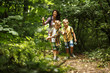Mother and her little sons  hiking trough forest . - 211148293