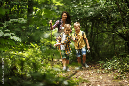 Mother and her little sons  hiking trough forest .