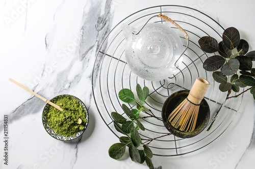 Fototapeta Ingredients for making matcha drink. Green tea matcha powder in ceramic bowl, traditional bamboo spoon, whisk on cooling rack, glass teapot, green branches over white marble background. Flat lay