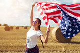 Young beautiful woman holding USA flag - 211158241