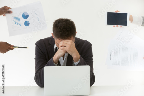 Leinwanddruck Bild Depressed male employee in despair exhausted by excessive workload and annoying colleagues, tired worker feeling fatigue suffering from work stress and headache trying to control emotions.