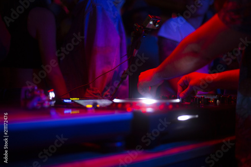 DJ tocando con tornamesas en discoteca