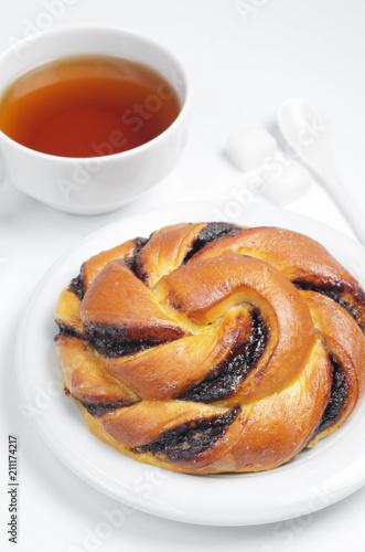 Fototapeta Bun and cup of tea