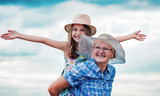 Childhood. Happy little girl and her grandmother enjoys together in a good mood. Family, lifestyle concept