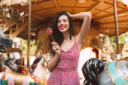 Fotobehang Amusementspark Beautiful lady with dark curly hair in dress standing with lolly pop candy in hand while happily looking in camera with carousel on background