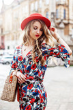 Outdoor portrait of young beautiful woman wearing stylish jumpsuit with floral print, red hat, wrist watch, necklace, holding straw bag. Model posing in street of old european city.