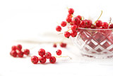 beautiful red currant berries from the garden in a glass bowl and on the table, background with copy space fades to white, close up - 211191633
