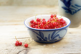 fresh red currant berries in a earthenware bowl on a rustic wooden table, copy space, selected soft focus - 211191826