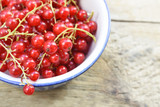 red currant berries in a bowl on rustic wood, close up shot with copy space - 211191872