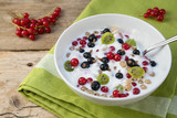 muesli with natural yoghurt, curd and fresh berries, healthy breakfast or dessert on a rustic wooden table - 211192021