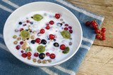 yoghurt and quark cream with fresh berries, healthy breakfast or dessert on a blue napkin and a rustic wooden table, view from above - 211192056
