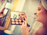 Woman in bathroom applying contour bronzer on brush - 211196836