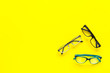 Glasses concept. Set of glasses with different eyeglass frame and transparent lenses on yellow background top view copy space