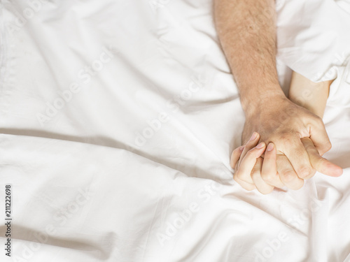 Sensual beautiful young couple is having sex on bed. Female hand pulling white sheets in ecstasy, orgasm. Love concept. Wellness. Couple in love. Orgasm concept. - 211222698