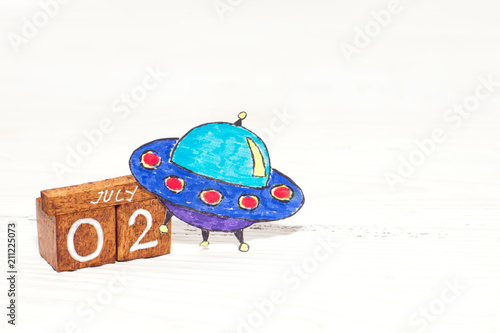 Fotobehang UFO Jule 2nd - World UFO Day on wooden calendar with funny picture of UFO
