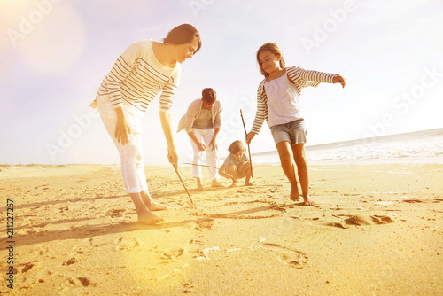 Family having fun writing messages on sandy beach - 211227257