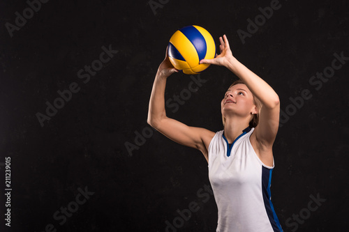 Girl playing volleyball on a dark background