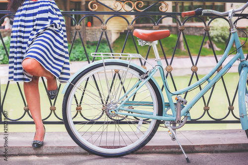 Fridge magnet Young girl standing near fence near vintage bike at park