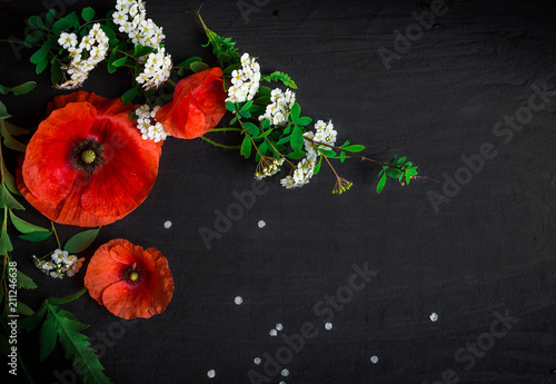 Fotobehang Klaprozen Bouquet of red poppies and white Spiraea on a black background. Wild flowers.