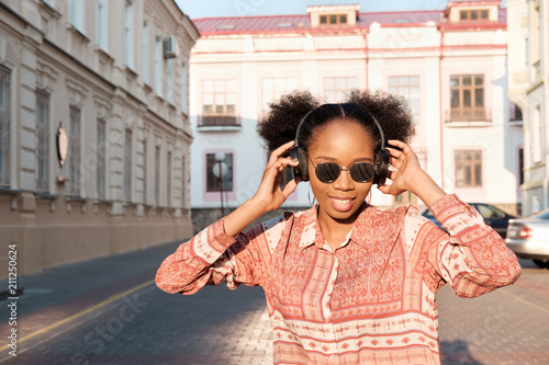 Black afroamerican girl has a walk in evening town and listening to music in headphones.  Girl in sunglasses in summer smiles and looking on sunset. - 211250624