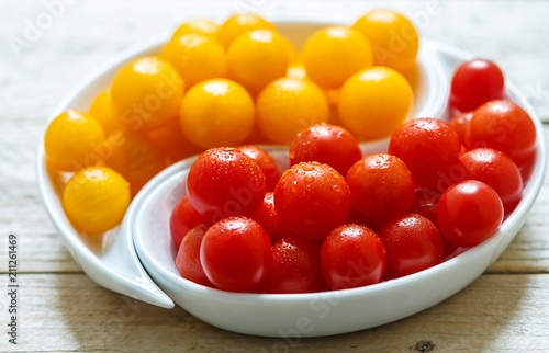 Aluminium Kersen Yellow and red cherry tomatoes with water drops. Fresh and juicy organic vegetables in a white plate on a wooden table