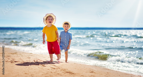 Boy and girl playing on the beach - 211264442