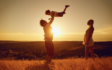 Happy family having fun playing at sunset on summer nature.