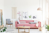 Real photo of a pink couch with pillows standing behind a table, next to an armchair, in front of a shelf with posters and flowers and under a lamp in bright and cozy living room interior