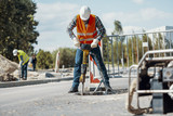 Worker in reflective vest with drill repairing street during roadworks © Photographee.eu