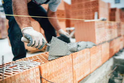Leinwandbild Motiv Professional worker using pan knife for building brick walls with cement and mortar