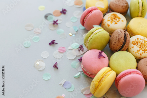 Fotobehang Macarons colorful macarons on trendy pastel gray paper with lilac flowers and confetti. tasty pink, yellow, green and brown macaroons. candy bar for party. food photography. yummy background