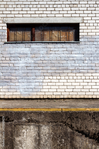 White brick wall with a boarded window