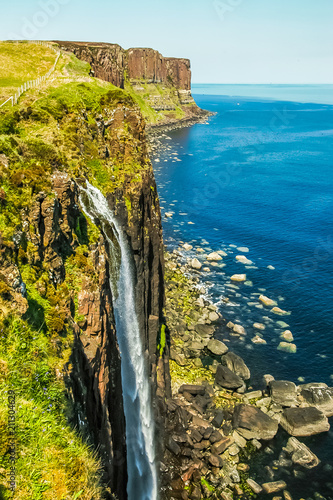 small waterfall flows into the sea on a rocky shore