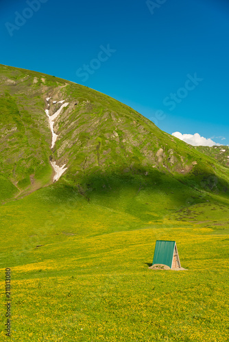 Fotobehang Pistache Mountain shelter on a green slope of the high big mountain. Alpine meadows in the Caucasus Mountains. Beautiful blue sky and clouds. Impressions from mountain tourism