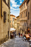 Narrow old street in Siena, Tuscany, Italy. Stone lane and typical architecture