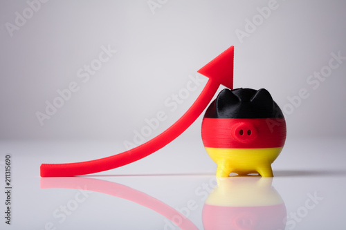 Close-up Of Piggybank Painted With German Flag And Red Arrow - 211315690