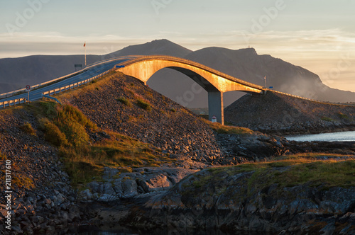 Foto Murales Atlantic road's curved bridge on sunset surrounded by calm water, fjords and rocky coast