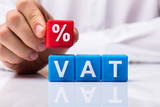 Person Placing Red Percentage Block Over Vat - 211318636