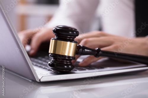 Fototapeta Wooden Mallet On Laptop Keypad