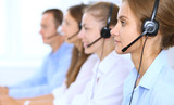 Call center operator in headset while consulting client. Telemarketing or phone sales - 211323635