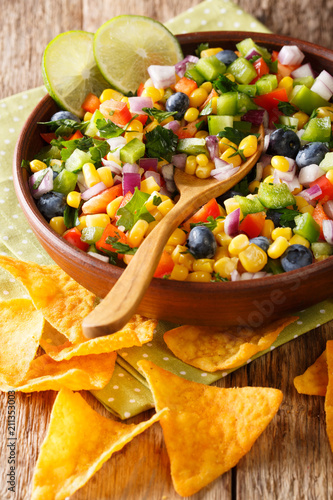 Salsa salad made from corn, blueberries, peppers and onions served with tortilla chips close-up on the table. vertical - 211353003