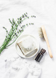 Homemade lavender soap, lavender flowers, face brush, essentials oil  on light background, top view. Flat lay - 211357044
