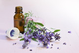 fresh lavender flowers and essential herbal oil in a glass bottle on light rose wood, copy space, close up - 211361608