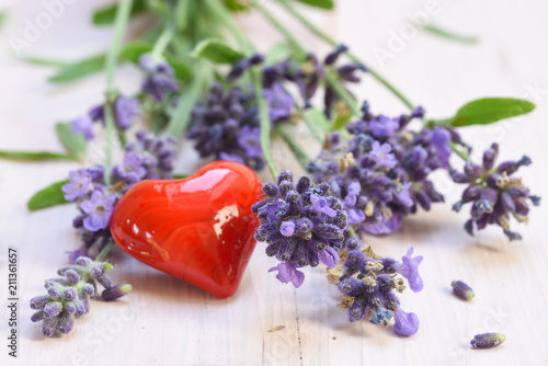blooming lavender and a red heart from glass on a white painted wooden background