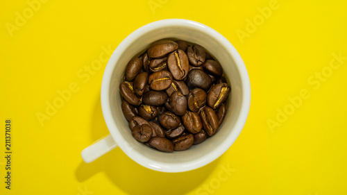 Fotobehang Koffiebonen A small coffee cup filled with fried coffee beans. Yellow background. Top view