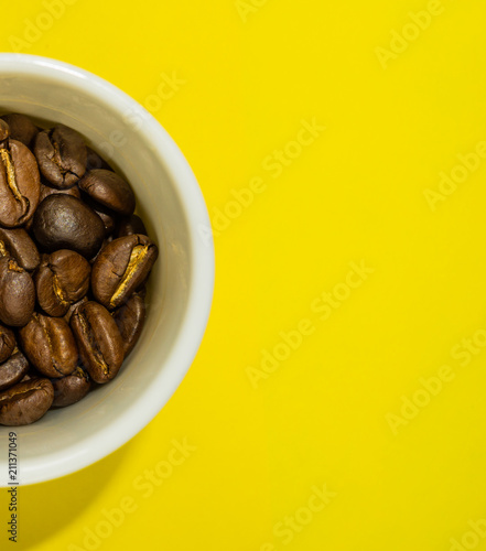 Aluminium Koffiebonen A small coffee cup filled with fried coffee beans. Yellow background. Top view