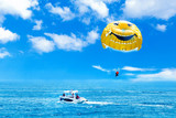 Parasailing water amusement. Flying on a parachute behind a boat on a summer holiday by the sea in the resort.