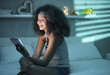 Leinwanddruck Bild - Hispanic Girl Watching Film With Tablet And Laughing